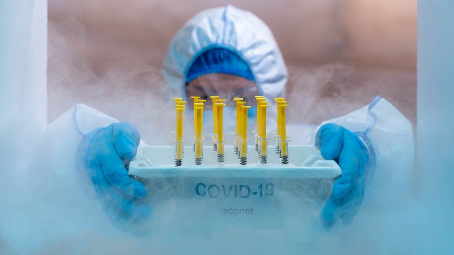 A specialist retrieving COVID vaccines from a freezer